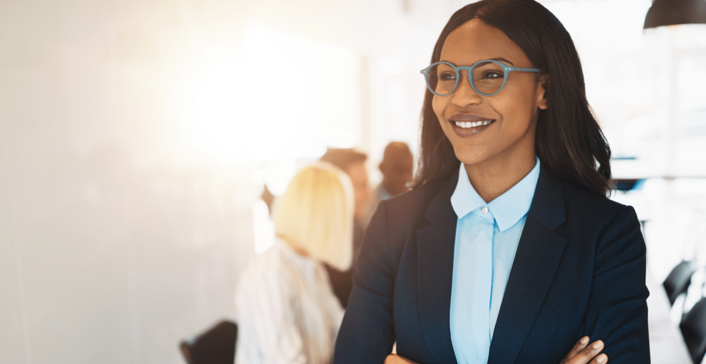 woman of color standing with arms folded in conference room showing confidence and positive self-esteem.